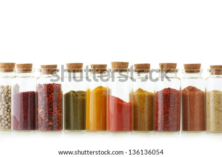Assorted ground spices in bottles on white background. - stock photo