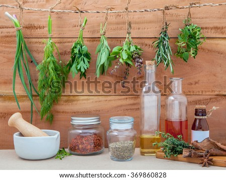 Assorted hanging herbs ,parsley ,oregano,sage,rosemary,sweet basil,dill,spring onion  and  set up with dry and fresh thyme ,olive oil ,sesame oil ,cinnamon and star anise  on wooden background. - stock photo