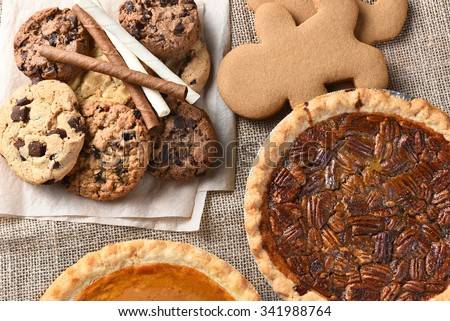 Assorted holiday desserts including:  gingerbread, pumpkin pie, pecan pie, chocolate chip and oatmeal raisin cookies,  - stock photo