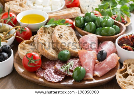 assorted Italian antipasti - deli meats, fresh cheese, olives and bread, horizontal - stock photo