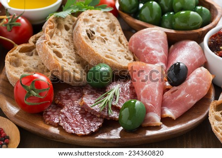 assorted Italian antipasti - deli meats, olives and bread, close-up - stock photo
