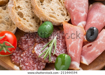 assorted Italian antipasti - deli meats, olives and bread, close-up, top view - stock photo