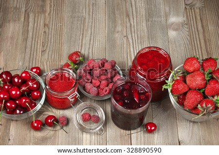 Assorted jams in glass jars and fresh berries in bowls on rustic wooden background. Top view point. - stock photo