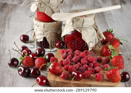 Assorted jams in glass jars with wood spoon and fresh berries on rustic wooden background. - stock photo