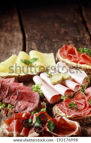Assorted meat and cheese sandwiches with rare roast beef, mortadella, ham, gouda, salami, on rye and wholewheat bread on a rustic wooden table with copyspace