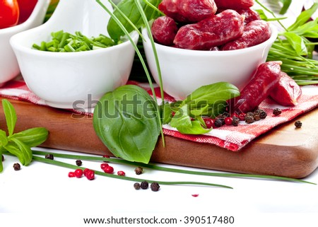 Assorted meats and sausages on a wooden board - stock photo