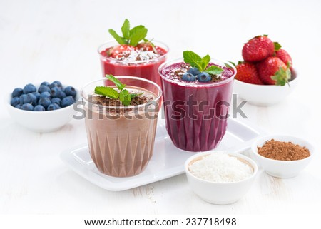 Assorted milkshakes - strawberry, blueberry and chocolate and ingredients, horizontal - stock photo