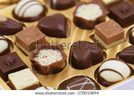 Assorted milky, white and pure chocolates, closeup  - stock photo
