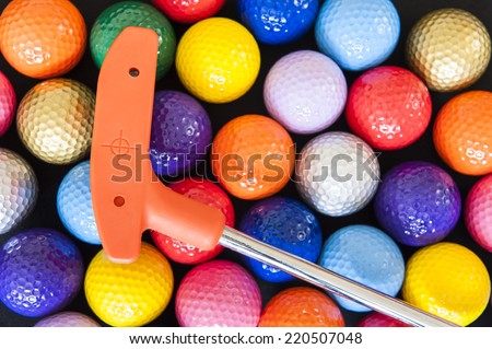 Assorted Mini Golf balls with an orange club - stock photo