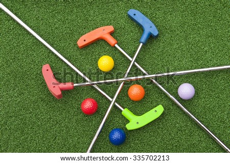 Assorted miniature golf putters and balls askew on synthetic grass
