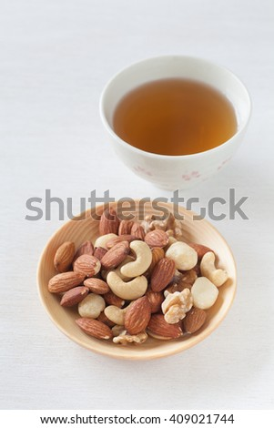 Assorted mixed nuts , Almond , Cashews nuts , macadamia , walnut with hot chinese tea - stock photo