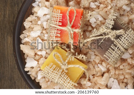 Assorted natural soaps and bath salt on dish. - stock photo