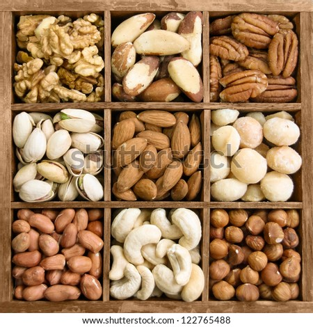 Assorted nuts in a wooden box (from top left: walnut, brazil nut, pecan, pistachios, almond, macadamia, peanut, cashew, hazelnut) - stock photo