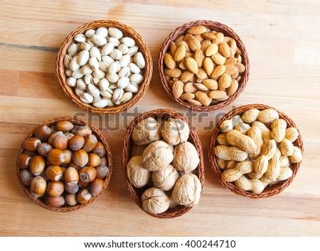 Assorted nuts in baskets: walnut, pistachios, almond, peanut, hazelnut - stock photo