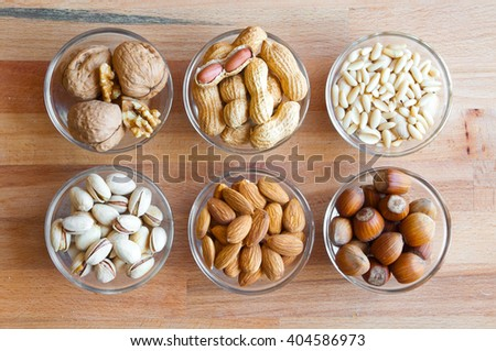 Assorted nuts in bowls: walnut, pistachios, almond, peanut, hazelnut, pine nuts