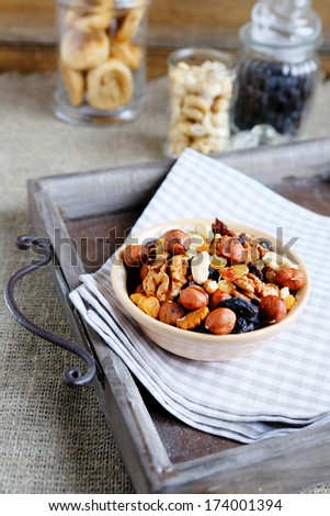 Assorted nuts in ceramic bowl on a tray, food closeup - stock photo