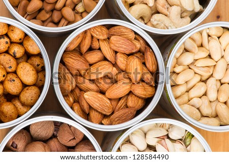 Assorted nuts in Iron pot (pecan, pistachios, almond, peanut, cashew,Pine nuts? - stock photo