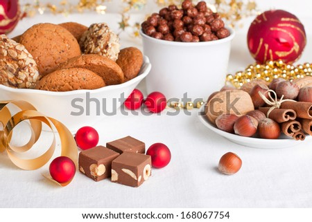 Assorted oatmeal cookies and chocolate candies with christmas decorations  - stock photo