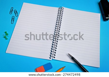 Assorted office supplies on blue background - stock photo
