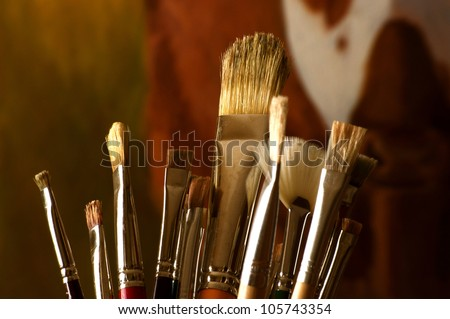 Assorted paint brushes with a painting in the background - stock photo