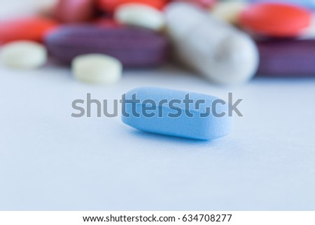 Assorted pharmaceutical medicine pills, tablets and capsules, close up of blue medicine pill.