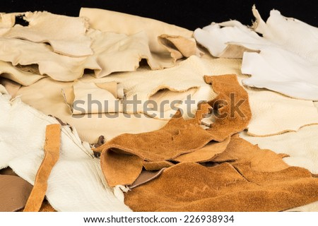 Assorted pieces of buckskin; doeskin; rawhide; and cured leather against black background. - stock photo