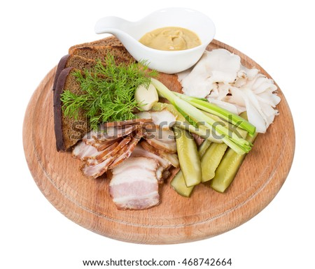 Assorted pork fat with pickles and mustard on wooden platter. Isolated on a white background.