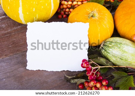 Assorted pumpkins with autumn leaves on wooden table. with card. - stock photo