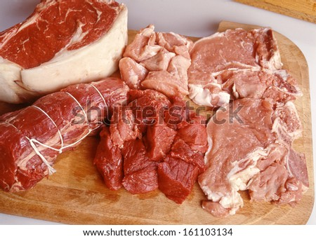 Assorted raw uncooked cuts of red meat displayed on a wooden board with beef and pork, high angle view - stock photo