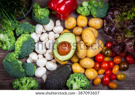 Assorted raw vegetables on wooden background