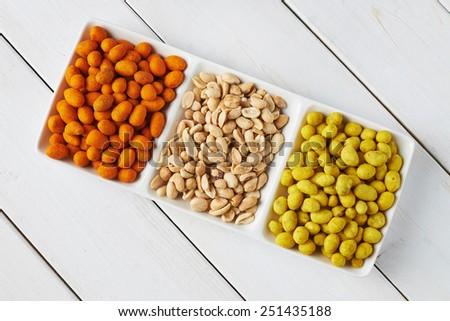 Assorted roasted nuts on white wood background. - stock photo