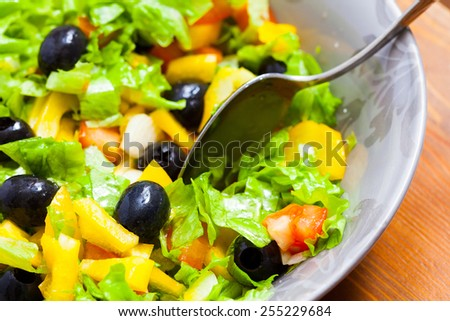 Assorted salad of green leaf lettuce with squid and black olives in bowl, close up - stock photo