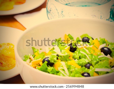 Assorted salad of green leaf lettuce with squid and black olives on lunch table, close up. instagram image retro style - stock photo