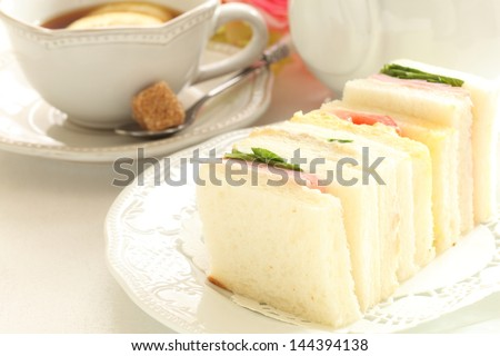 assorted sandwiches in square size and lemon tea - stock photo