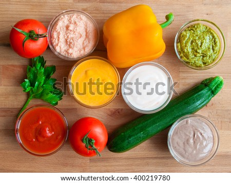 Assorted sauces in glass bowls on wooden table with vegetables - stock photo