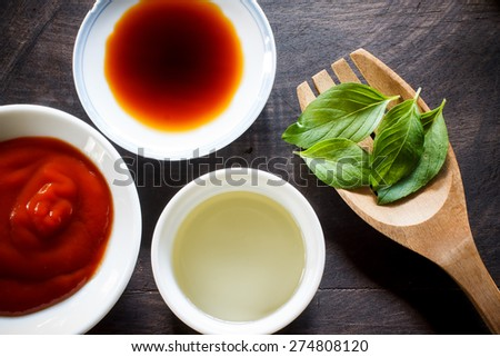 Assorted Sauces prepare for cooking in small plate with basil put on black old wooden - stock photo