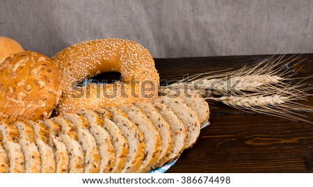 Assorted seeded breads on a rustic table with sliced wholegrain bread, a sesame bagel and cheese bun with ears of ripe wheat alongside and copy space - stock photo