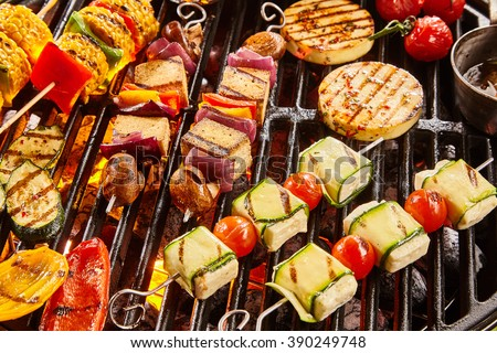 Assorted shish vegan or vegetarian kebabs with tofu and haloumi grilling on a grill over barbecue with colorful tomatoes and bell peppers, onion and eggplant for a tasty summer picnic - stock photo