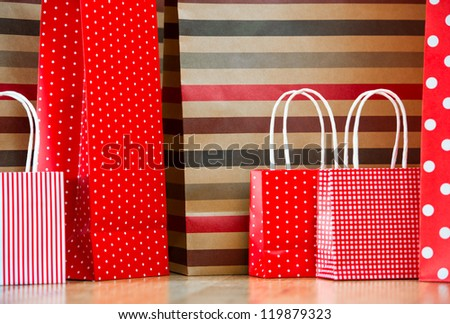 Assorted shopping and gift red paper bags - shopping and holiday concept