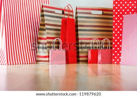 Assorted shopping and gift red paper bags - shopping and holiday concept with copyspace - stock photo