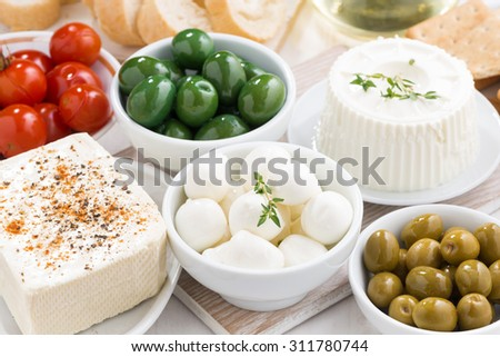 Assorted soft cheeses and pickles on table, horizontal - stock photo