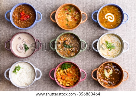 Assorted soups from worldwide cuisines displayed in bowls in three colorful lines garnished with cream and herbs in a World Of Soup concept, overhead view - stock photo