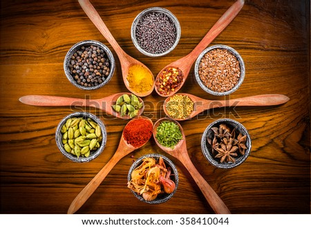 Assorted spice spoons and bowls arranged in circular pattern - stock photo