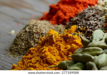 Assorted spices and dry herbs on wooden background - stock photo