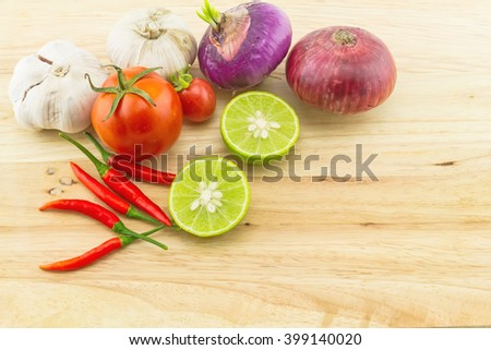 assorted spices for hot and sour soup (Tom Yam) lemon ,red chilli ,onion , garlic and tomato on wooden block - stock photo