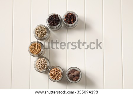 assorted spices in a glass container form alphabet c - stock photo