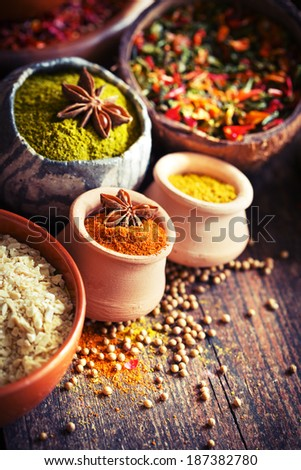 Assorted spices in small containers  on wooden rustic background  - stock photo