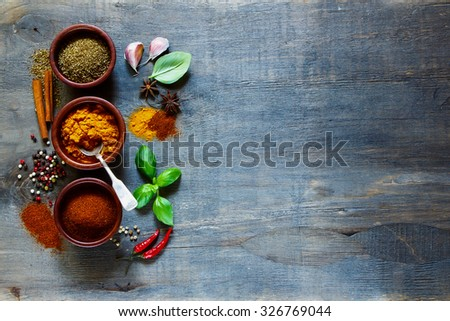 Assorted spices in small wooden bowls. Food and cuisine ingredients. Cooking background with space for text. - stock photo