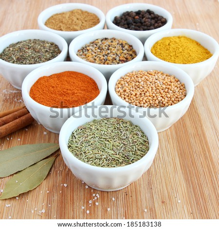 Assorted spices in white bowls - basil in the foreground