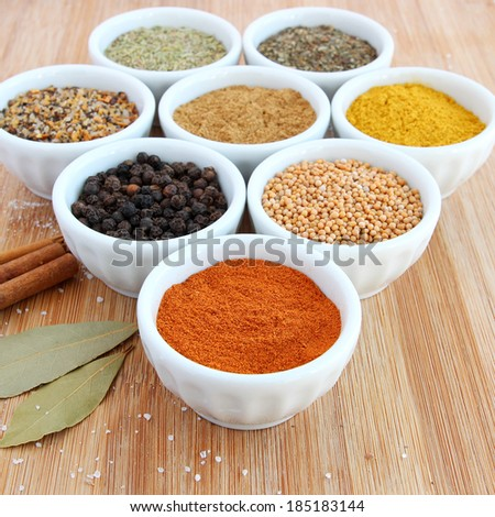 Assorted spices in white bowls - paprika in the foreground